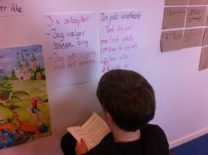 En elev har valgt sit læsested. I baggrunden ses oversigter fra mål, vi har arbejdet med.