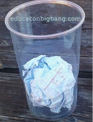 colocación de la pelota de papel en el fondo del vaso