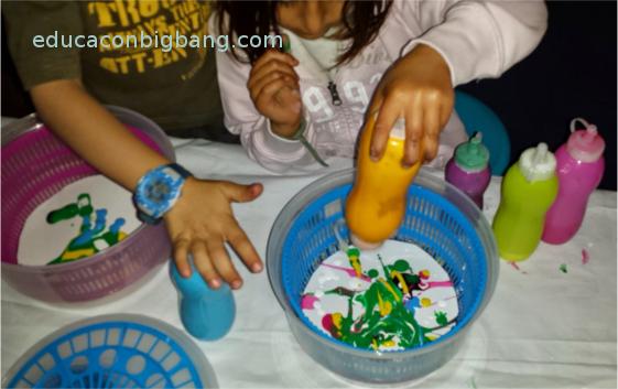 Niños echando pintura en el escurridor