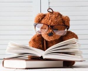 stuffed teddy bear reading a book