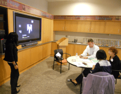 A student introducing her documentary to a team of judges