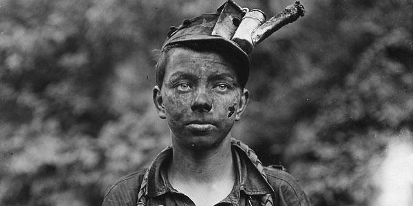 Boy with dirty face and kerosene headlamp on his head