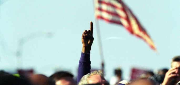 Hand raising in the air in front of an American flag at a march at the Edmund Pettus Bridge in Selma, Alabama, in 2000