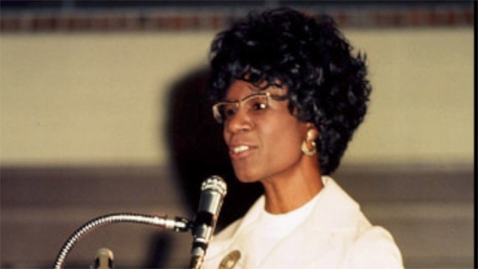 Shirley Chisholm speaking at a microphone