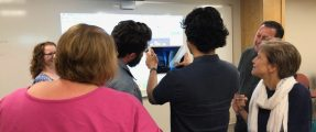 Three men and three women experimenting with an AR app on an iPad
