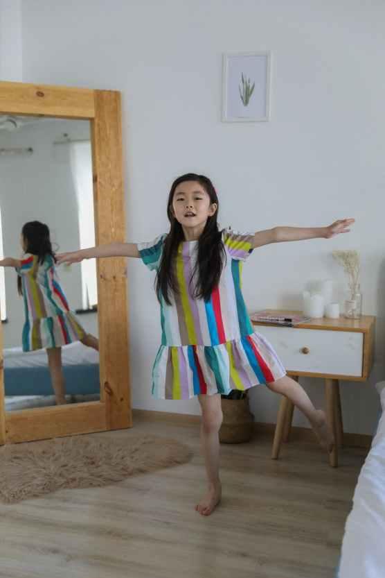 cute asian girl in bright dress balancing on leg