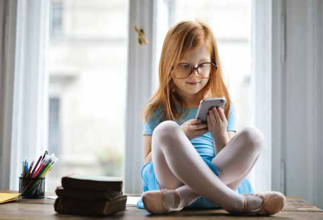 girl wearing blue dress while using smartphone