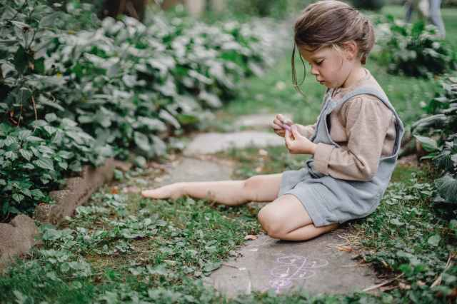 cute stylish child playing with chalks in the garden