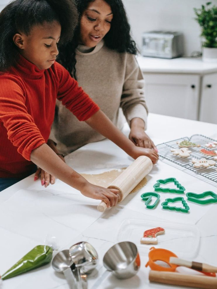 crop black girl rolling out dough while helping mother
