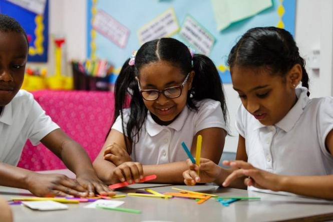 children in the classroom using making numbers manipulatives