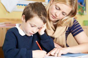 child and teacher writing