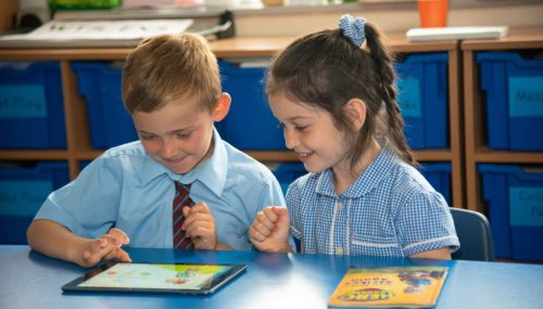 Primary children reading a book and a tablet