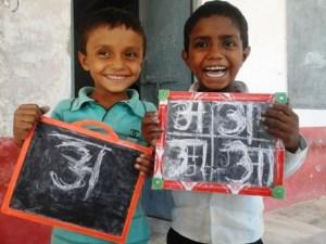 सरकारी स्कूल में पढ़ने वाले बच्चे अपना लिखा हुआ दिखाते हुए।