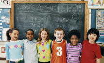 Children standing in front of a chalkboard.