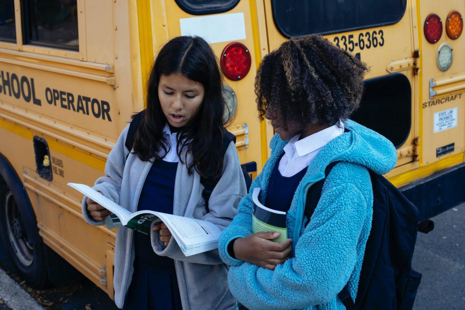 multiracial little girls near school bus