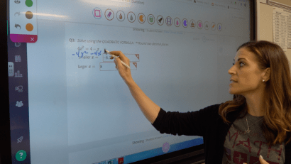A member of the math PLC goes through student replies on the smart board.