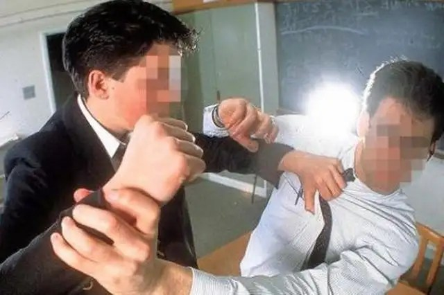A pupil violently attacking a teacher in a classroom