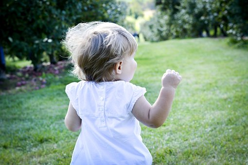 Petite fille courant dans l'herbe