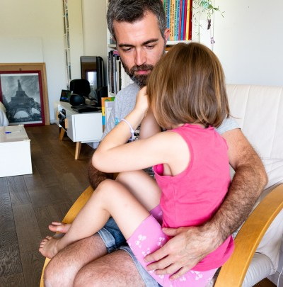 Un papa qui console sa fille assis dans un fauteuil