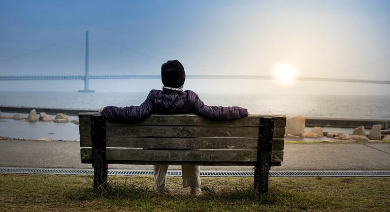 Homme se reposant sur un banc devant un pont