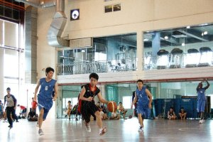 UCSI students playing basketball at the Multipurpose Hall with the Gym in the background.