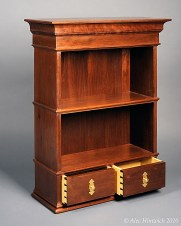 """This classically proportioned wallhung cabinet is made primarily of Peruvian walnut and secondarily poplar. The finish is shellac and wax. The length and width of the cabinet follow the """"golden rectangle"""". The vertical proportions are after the Doric Order seen in classical architecture. The shelves comprise the pedestal; the shelves, the column; and the crown, the architrave. The back is tongue and grooved. As with the other wallhung cabinets shown here, this cabinet is designed to be hung from the wall with a French cleat."""