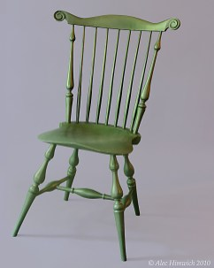 Popular during the 18th and 19th centuries, Windsor chairs have seen a resurgence in interest. The unique feature of this fanback Windsor chair is the carved whorls in the crest rail. Several woods are used: pine for the seat, red oak for the spindles and crest rail, and maple for the spindle posts and baluster turnings. The finish is milk paint (Lexington Green) and tung oil.