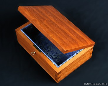 This jewelry box with through dovetails and mortised lock is made of Honduran mahogany with a shellac finish. It is lined with a blue brocade and mirror backing.