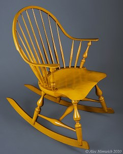 This continuous arm Windsor rocking chair The unique feature of this fanback Windsor chair is the double curve arm which constitutes the back and the arms of the chair and rockers. Several woods are used: pine for the seat, red oak for the spindles and rockers, white oak for the continuous arm, and maple for the arm posts and baluster leg turnings. The finish is milk paint (Mustard yellow), tung oil, and shellac.
