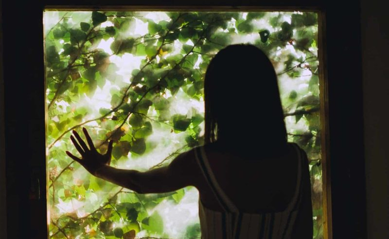 Vrouw raakt glas aan en kijkt naar buiten
