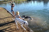Sisters Kendra and Malika Otsmane play with their dogs Annie and Lucky in the lake at Steele Indian School Park in Phoenix, Arizona on January 31, 2017.