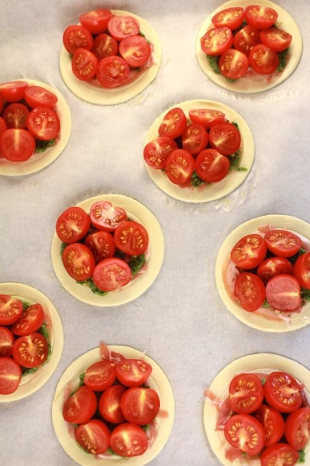Taartjes met gehalveerde tomaatjes beleggen