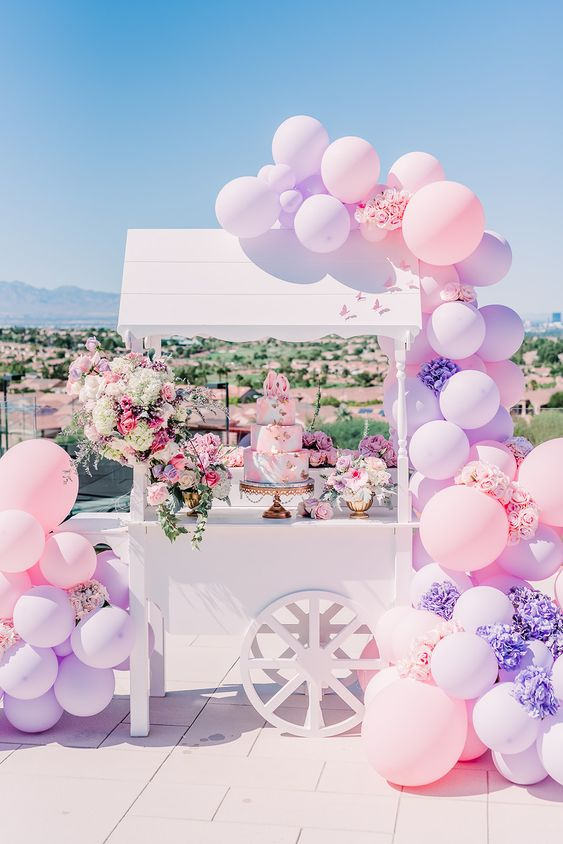 white candy cart with pink and purple balloons