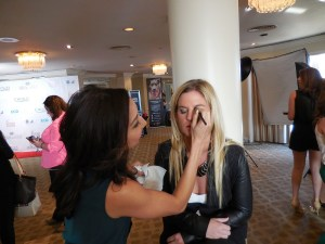 Makeup artist Maria Lee applies makeup to author and journalist Liz Crokin