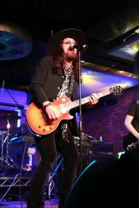 Damon Fox from Stormtrooper on vocals and guitar with Okai Sisters. Photo courtesy the Experience Magazine