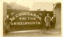 Photograph of the entrance gate to W.Cooke & Son Smiths and Wheelwrights Sewardstone Street Waltham Abbey local wheelwright next to old wooden 16th century house opposite Essex