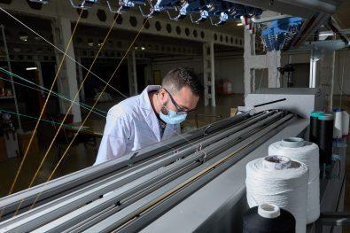 ALCOI (ALICANTE), 05/07/2021.- El Instituto Tecnológico del Textil ha desarrollado el proyecto TPTEX 2.0 mediante el que producen unas prendas compresivas para el tratamiento de enfermedades como el linfedema o el lipedema cuya principal novedad es que son de uso exterior, como leggings normales. En la imagen un técnico controla la máquina en la que se tejen los diferentes modelos. FOTO: EFE/ Natxo Francés