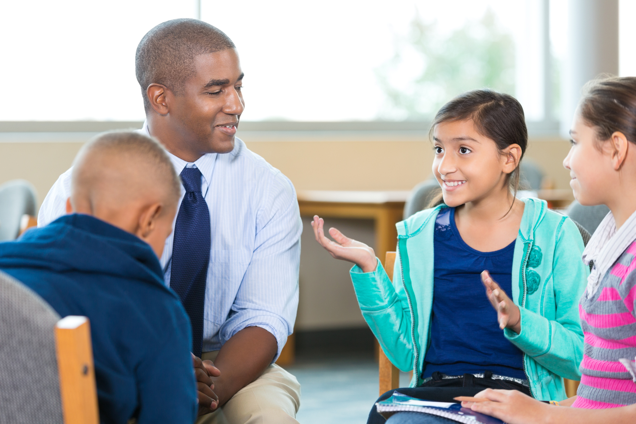 Elementary Age Kids Talking To Counselor During Group
