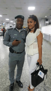 Gifty strikes a pose with customs boss at the airport before she jets home