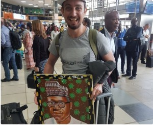 Oyinbo man spotted with Buhari's painting at Lagos Airport. See what he said