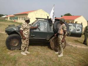 Soldiers Pose With Terrorist's Dead Body After Repelling Boko Haram Attack. PICS