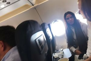 Katie Price and her toyboy lover drink alcohol and tonics on a morning flight