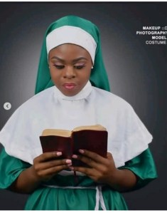 Pretty lady dressed as a nun in Nigerian colour reading bible to celebrate 58th independence day.