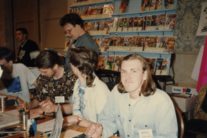 Jeff 'smiling' for the camera. Note the pile of prints in front of my spot on the table. Don't note my mullet.