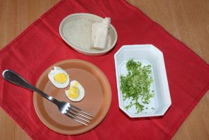Plate and bowls filled with a hard-boiled egg, breadcrumbs and chopped salad.