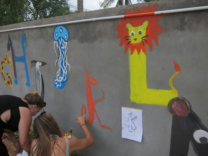 Volunteers painting the wall - animal letters.