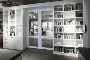 white gloss bookcases with hidden storage flanking a double door