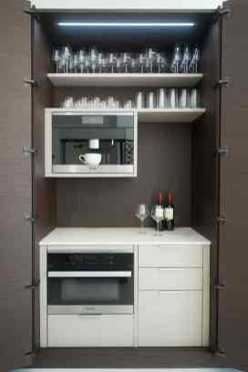 hidden coffee bar featuring plate and cup storage as well as a microwave hides away behind smoked oak doors