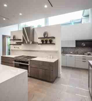 floating wall with stove and display shelves that hides the catering kitchen of a washington coalition memorial park area home in houston renovated by chavez