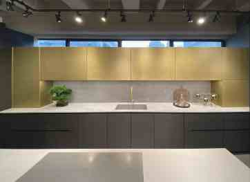 eggersmann ny kitchen display goosneck sink in niche with ventura brass finish on upper cabinets and dark sisal veneer on the lower cabinets